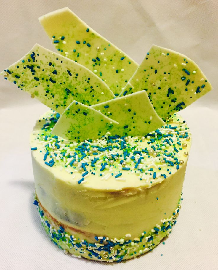 White Chocolate buttercream cake. Blue and green sprinkles, chocolate shards
