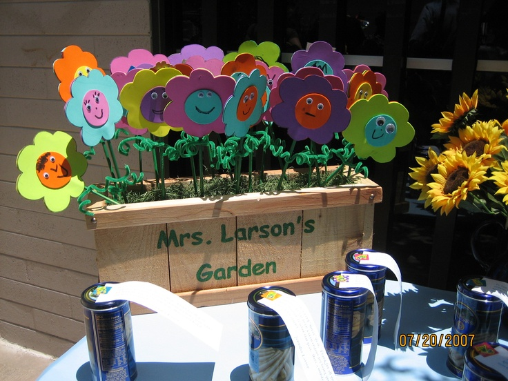 Giftcard Garden for Kindergarten Teacher. Made from art foam sheets, thin wooden dowels for stems. Flowers are 2 stuck together to make a pocket - you can then insert notes and giftcards in them. Each child made their own flower with faces and googly eyes.