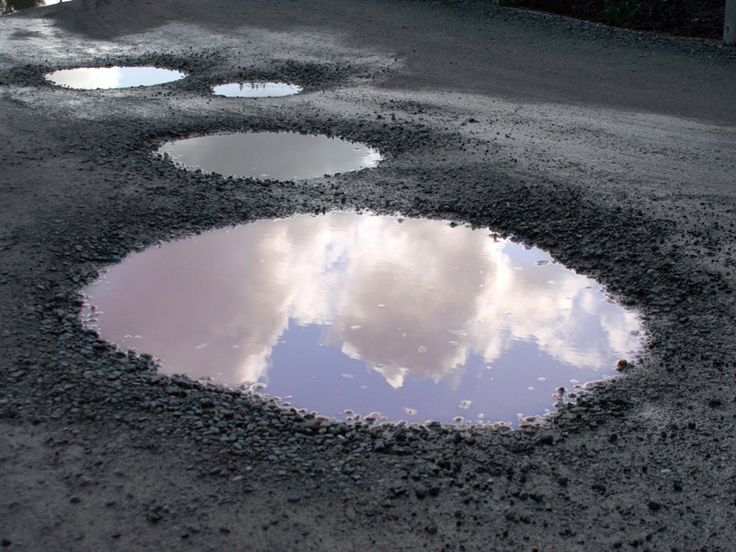How are potholes created? Potholes occur when moisture penetrates cracks in the asphalt surface of a road or driveway. Cold weather freezes the water and causes it to expand. A pothole forms when dirt and gravel is forced out leaving a hole. The Ice eventually melts and the stressed asphalt becomes a pothole.