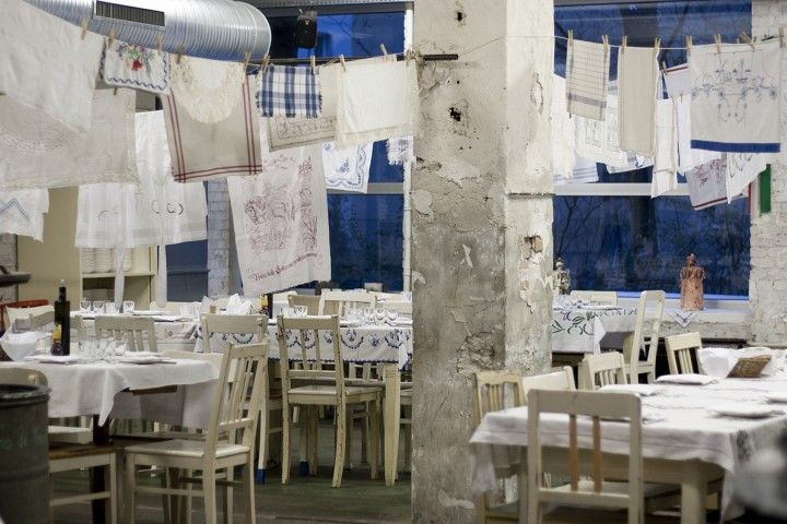 A series of white painted wooden tables stand under a cover of old embroidered cloths hanging from the ceiling, as if they were left there to dry.