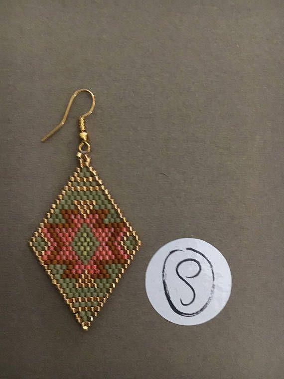 Boucles doreilles entièrement tissées à la main en perles miyuki. Elles sont dans les tons kaki, orange et doré. Elles sont de style ethnique Elles sattachent par des crochets en métal doré Largeur: 3,4cm Longueur: 6,5cm