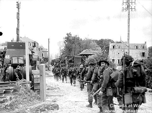 D-Day, Juno Beach - Tanks and Regiment de la Chaudiere moving along French village road, Normandy Beach head. 6 June 1944.