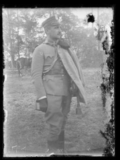 Klisza przedstawia oficera pułku ułanów Legionów Polskich - mężczyznę w średnim wieku, stojącego na tle drzew widocznych w oddali, zwróconego 3/4 ku prawej, ujetęgo poniżej kolan, z bliskiego planu, w pionowym kadrze. Oficer ubrany jest w kurtkę mundurową i ułankę z futrzanym kołnierzem zarzucona na lewe ramię, bryczesy wpuszczone w cholewy butów i w czapkę maciejówkę z orzełkiem legionowym. Na dłoniach ma ciepłe rękawice. Twarz o regularnych rysach, z prostym nosem, ciemnymi, krótko prz...