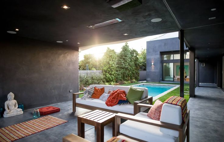 Um nicho na construção foi transformado em uma sala. Em frente à piscina, o espaço ganhou futon e estátua em um cantinho reservado para o relaxamento