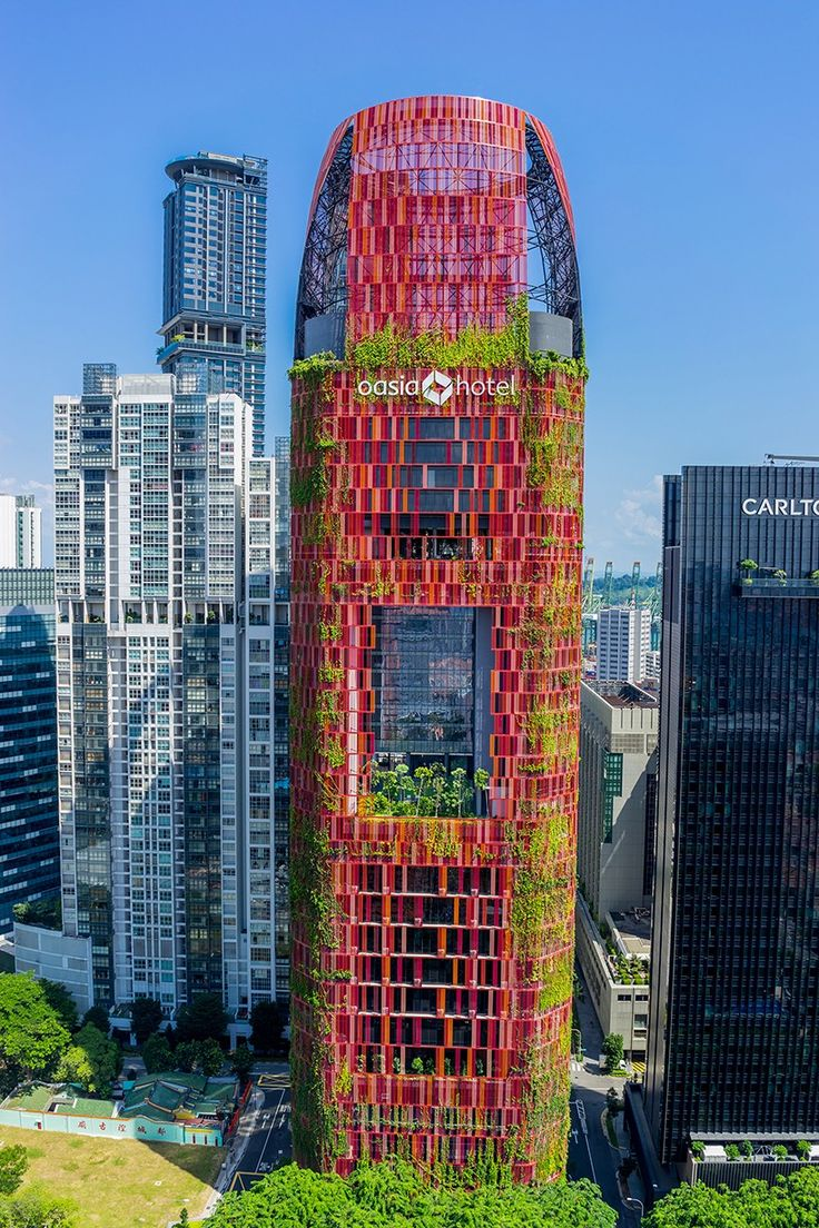 the verdant hotel tower is clad in a mosaic of red aluminum mesh paneling that has allowed the integration of 21 species of creepers, plants and flowers.