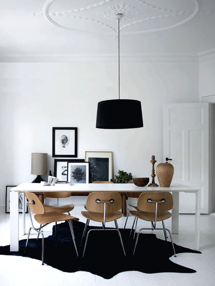 Dining room with black drum shade chandelier, black hide rug, white dining table, plywood chairs, b/w photos