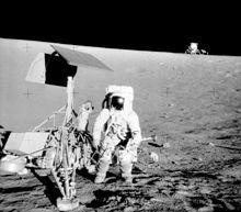 Pete Conrad, commander of Apollo 12, stands next to Surveyor 3 lander. In the background is the Apollo 12 lander, Intrepid.