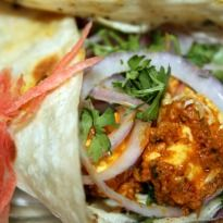 Paneer Tikka Kathi Roll: Juicy paneer tikkas topped with green chutney and onions and wrapped in egg parantha made with a fresh dough.
