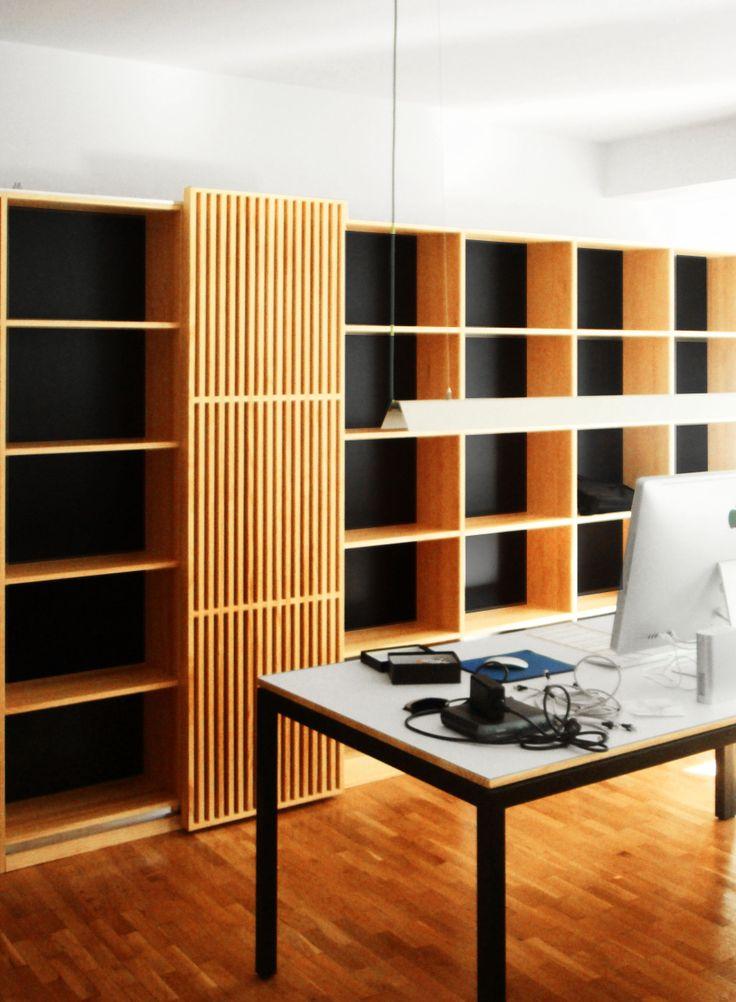 Detalle de la zona de trabajo con estanterías y puerta corredera listonado. Diseño y reforma de 08023 Arquitectos - Barcelona