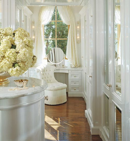 This closet is light and airy.  The warm wood flooring contrasts with the white of the built-ins and molding and the creams and yellows of the flowers and drapery.  It is a very classic and elegant look.