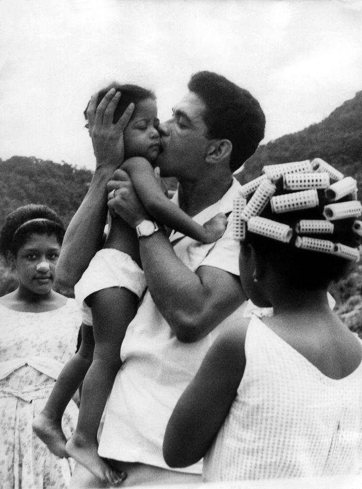 This may well be the most amazing photo ever taken. Garrincha looks like he's about to eat that baby! And look at the other girls: one's in curlers and the other is wearing one of those Breathe-Right strips thirty years before they came on the market.