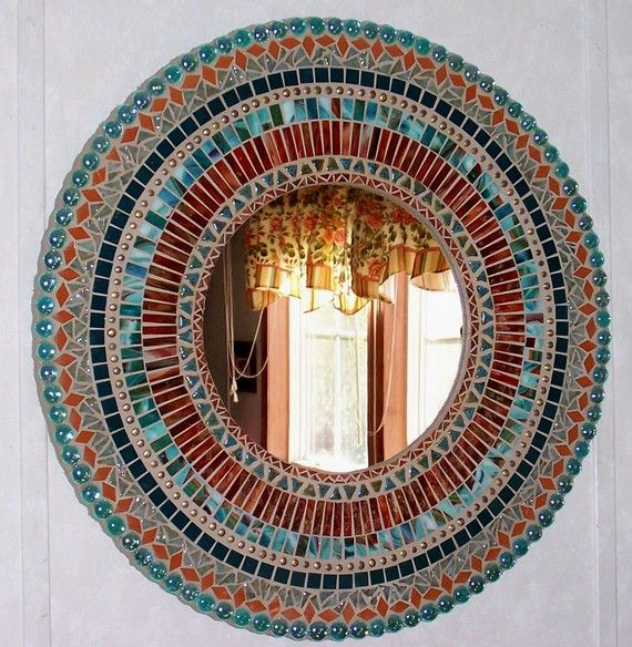 This mosaic mirror was created using teal, aqua, adobe, and deep red/orange (rust) stained glass, glass gems, upholstery nails, and ceramic