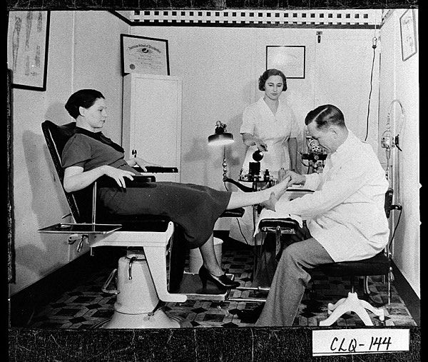 Moultrie, ca. 1936. Doctor H. D. Wilson, chiropodist, examines a patient's foot while his nurse looks on. Note the chairs of doctor and patient, the equipment on the desk, and the light fixture, all typical of this period of history. Doctor Wilson's office was located on the courthouse square. Digital Library of Georgia Georgia Archives