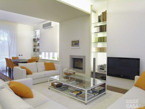 Il divano angolare e quello a due posti, rivestiti in tessuto bianco, sono di Molteni  C., come le poltroncine e il tavolo in wengé della zona pranzo, sistemato di fronte alla cucina