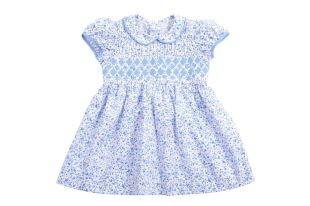"""Vestido para bebe niña elaborado con tela estampada de florecitas azules. Cuello redondo y mangas cortas semi bombachas. Detalle al frente con bordado """"nido de abeja"""" en azul y blanco."""