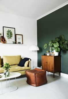 Emerald green accent wall in white living room with walnut furniture, yellow couch, and floating shelf with photographs displayed on it
