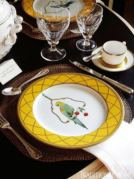The yellow and gold details of the whimsical bird pattern plates stand out against a black tabletop. - Traditional Home ® / Photo: Werner Straube / Design: L. Jonathan Savage