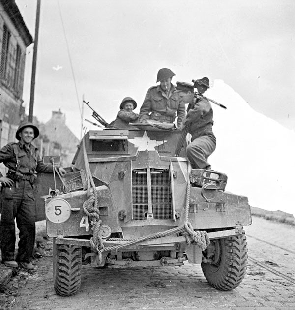 Canadians capture Caen - Lieutenant George Cooper, Canadian Army Film and Photo Unit, talking with Captain R.T. Miller, his brother-in-law, who is aboard a Humber light reconnaissance car, Caen, France, 11 July 1944.