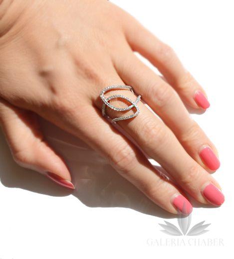 Regulowany pierścionek (minimalny rozmiar 10) wykonany ze srebra rodowanego próby 925. Wyrób wysadzany cyrkoniami o szlifie brylantowym. Szerokość maksymalna zwzoru to około 2,1 cm.