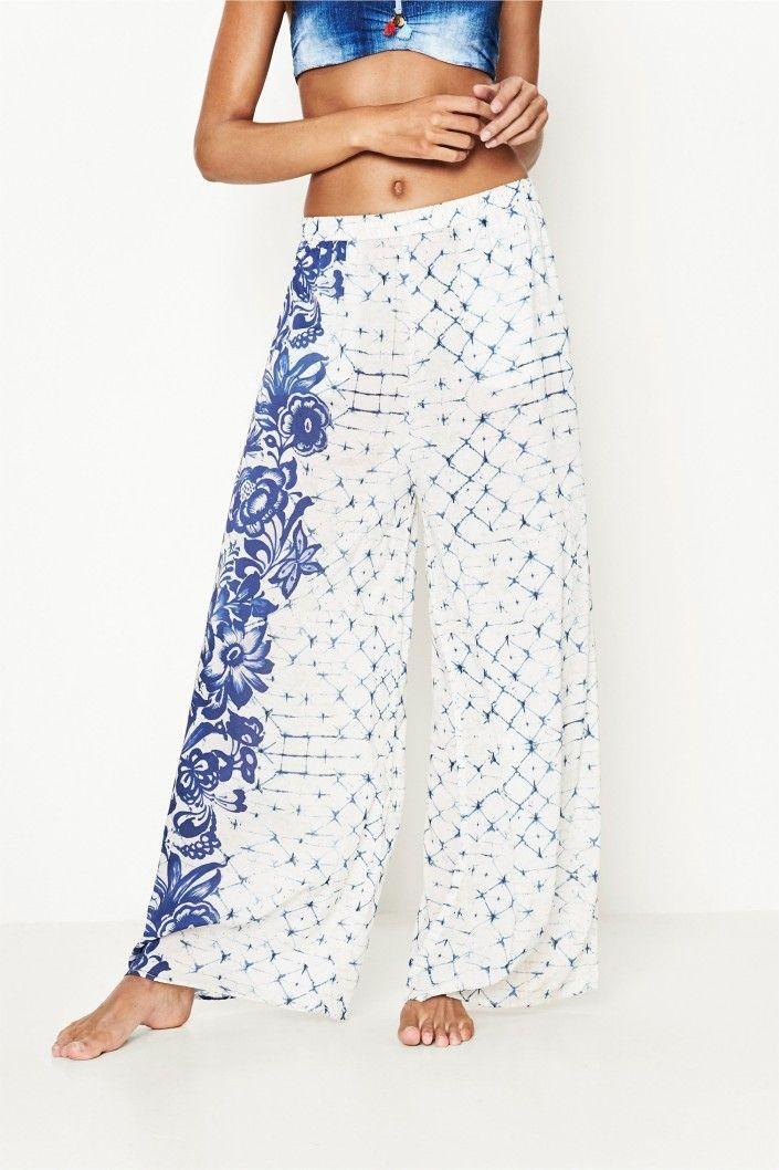 Bílé splývavé kalhoty s modrým potiskem. Na pravé nohavici originální květinový motivVnější materiál: 100% viskóza