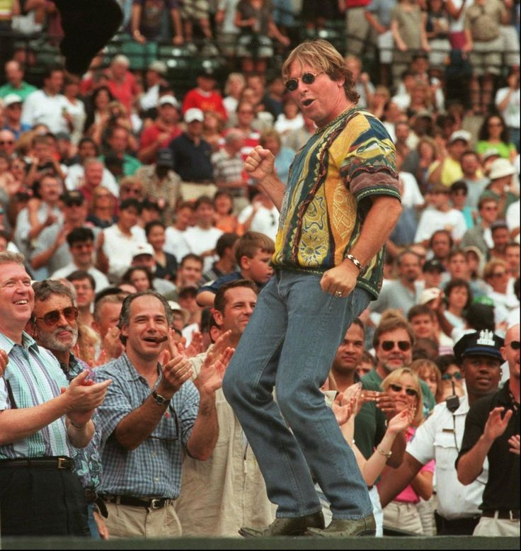 """John Denver dances atop the Orioles dugout as he sings his rendition of """"Thank God I'm a Country Boy"""" in a Sept. 20, 1997, file photo, during an Orioles game at Oriole Park at Camden Yards in Baltimore, Md. Denver was killed when his experimental plane crashed into Monterey Bay, Calif., Sunday, Oct. 12. (AP Photo/Baltimore Sun, Doug Kapustin)"""