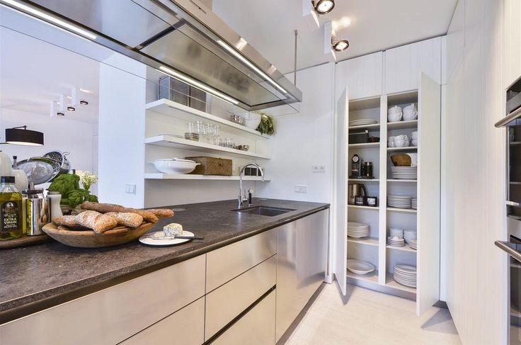 Nerezový modul kuchyně Varena s digestoří a pracovní deskou z flambované žuly doplňují bílé karvrované skříňky (jakoby krájený deskovitě členěný povrch). Kuchyň je vybavena spotřebiči Siemens.