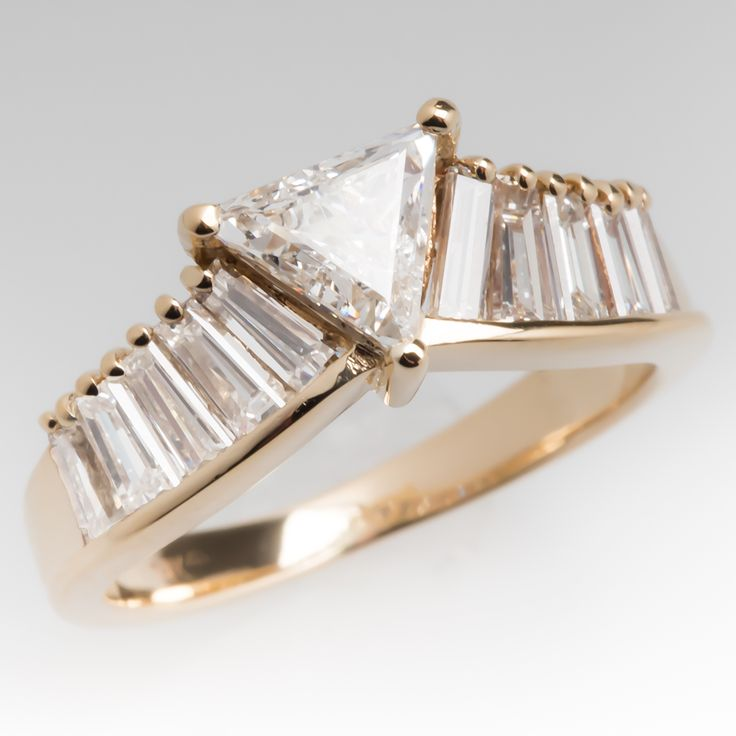 This unique ring features a 1/2 carat triangle center diamond with baguette accents. It is an incredible design and the diamonds are all high quality. The ring is crafted of solid 14k yellow gold