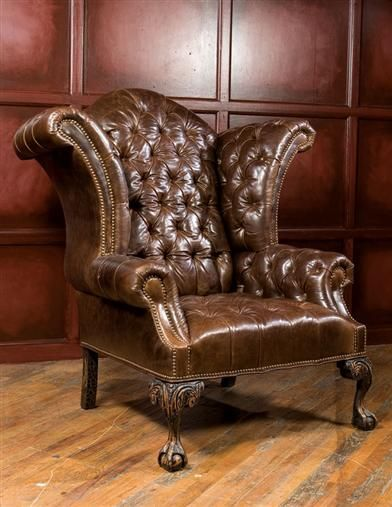 """CLASSIC LEATHER WINGBACK CHAIR A distinguished chair worthy of a queen's posterior offers tufted pillows that absorb ones tired muscles and assuage with buttery softness. Hand carved feet, brass studs. USA. 53 x 45""""."""