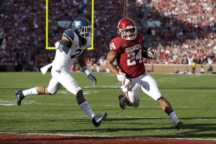 Oklahoma's Rodney Anderson (24) scores a touchdown in front of West Virginia's Kenny Robinson (2) during a college football game between the Oklahoma Sooners (OU) and the West Virginia Mountaineers at Gaylord Family-Oklahoma Memorial Stadium in Norman, Okla, Saturday, Nov. 25, 2017. Photo by Bryan Terry, The Oklahoman