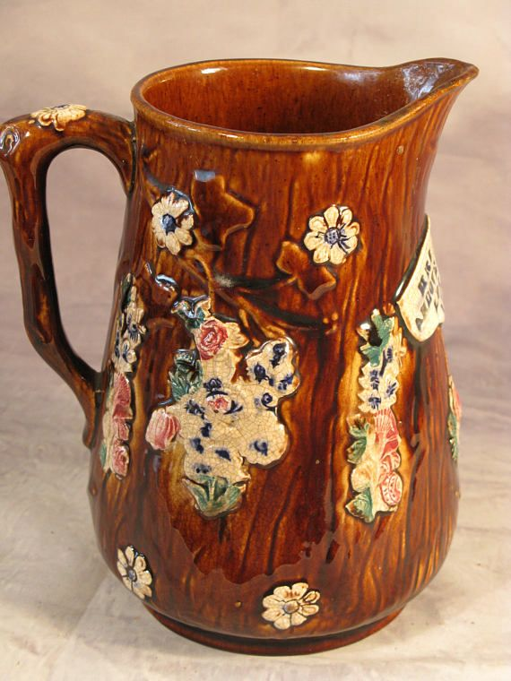Antique Victorian Vintage English Measham Bargeware WaterJug Dated 1886  A late 19th Century Victorian period Measham treacle glazed barge ware water jug. Decorated in the traditional English style with colourful floral arrangements. This ornate jug would probably have been a gift from the bargees wife marked in central cartouce Mrs Petts Andover RD London 1886 The other remember me Dimensions: 8 1/4(21cm) and 6 1/2(16.5cm) wide 19th century Measham Bargeware pottery. Bargeware was ...