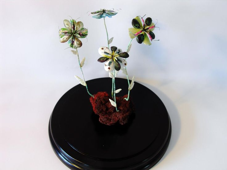 Erupting Flowers, DIA24 x H28 cm, in glassdome, 2016  by Iben Toft Nørgård.  'Erupting Flowers' is the result of studies on Vestmannaeyjar, Iceland, more specifically Heimaey where I made geological research and tried to learn about, or rather imagined how plant life could have evolved after the violent eruptions from the 'Eldfell' volcano in 1973. The flowers in the work are cut and created entirely from illustrations of animals.