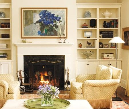 Built-in shelves display books and art; a large still-life painting hangs above the fireplace flanked by large, overstuffed chairs trimmed with a deep fringe in this inviting space.