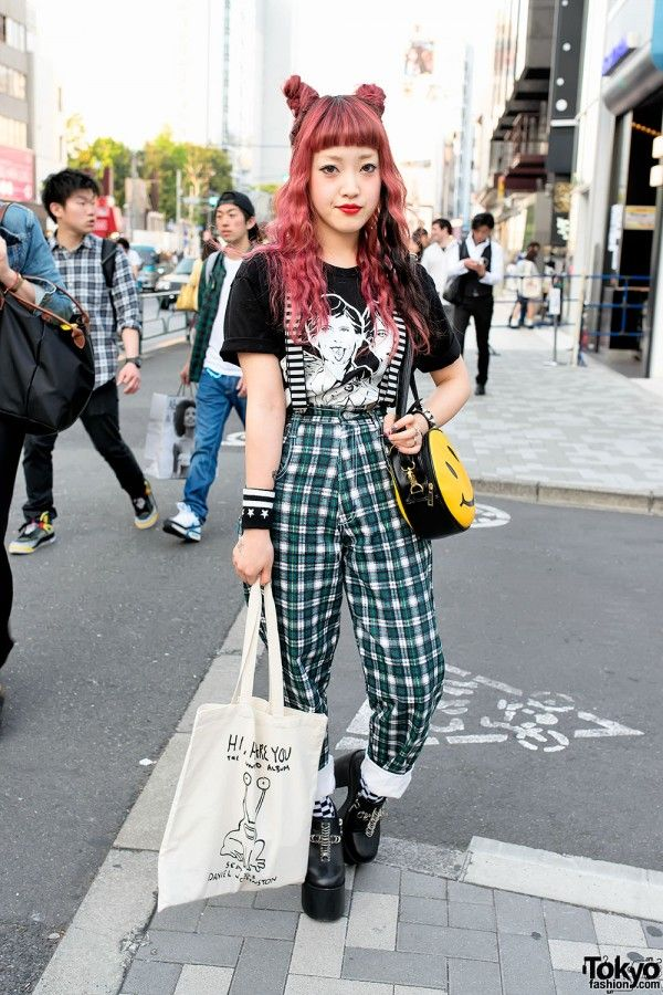 Cocomi is a Japanese fashion blogger and staffer at the LaForet Harajuku boutique Vlli Vlli. Cocomi is wearing a Bad Acid t-shirt with striped suspenders, plaid pants from the Harajuku resale shop SANKAKU, checkered socks, and Unif platform booties. Accessories include a smiley face bag from Bubbles Harajuku, a Daniel Johnston tote bag from Kinsella Harajuku, studded bracelets from HellcatPunks, and several temporary tattoos. (Tokyo Fashion, 2014)