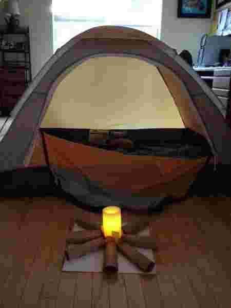 Une tente et un faux feu de bois en intérieur