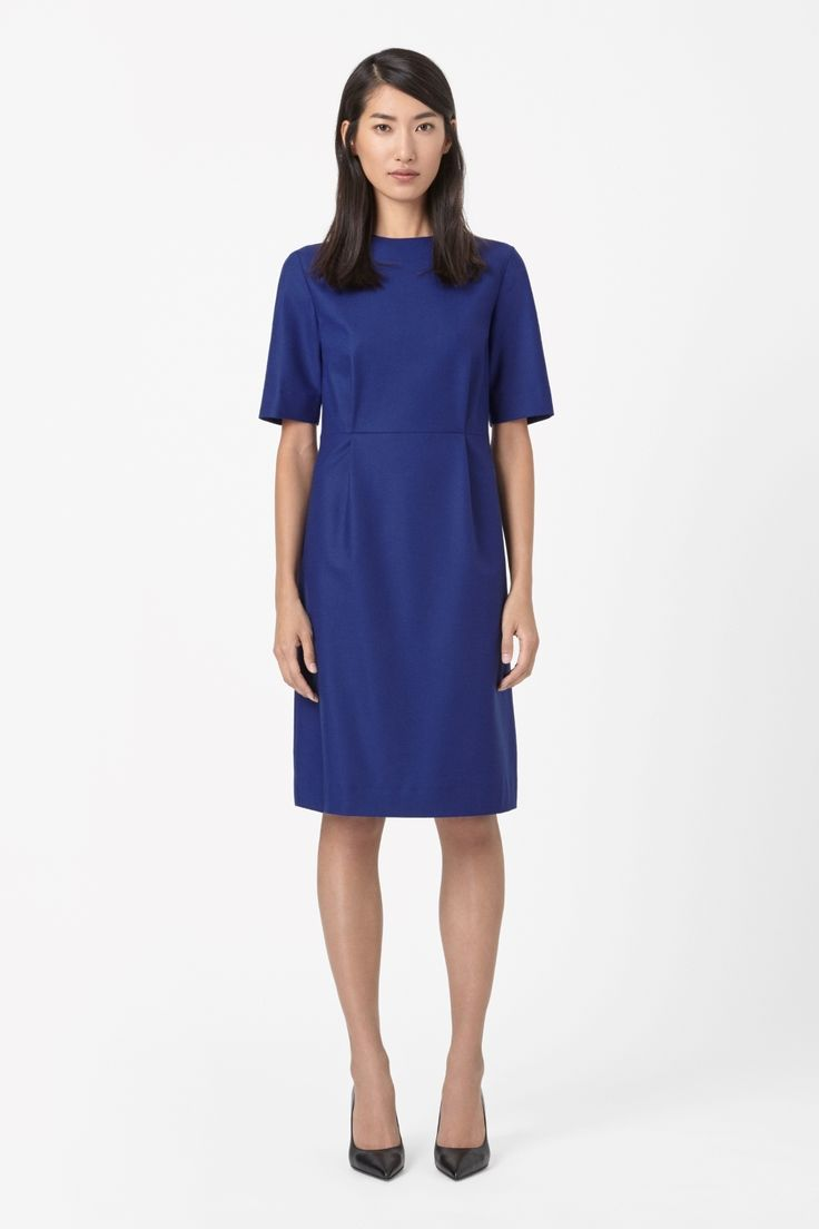 Made from soft unlined wool, this dress has a raised round neckline. Pleated at the front for a lightly fitted waist, it is a half-sleeved style with cleanly finished edges and a hidden back zip fastening.
