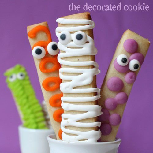 15 CUTE AND EASY HALLOWEEN TREATS Monster Cookie Sticks (via The Decorated Cookie) Bake cookie dough into sticks and have fun decorating your own bright and colorful monsters.