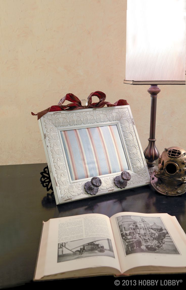 For this DIY decor,  remove the glass from the frame, and replace it with batting-backed fabric. Then add the embellishments of your choice—say, wired ribbon and a clear glass knob.