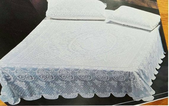Delicate looking intricate fine lace bedspread with scalloped edges. Drapes perfectly on a queen size bed as shown in the picture. Available in 2 colors - white and ecru The 1st 2 pictures are of the white bedspread and the last 3 pictures show the light ivory color bedspread. Can be used as a table cloth as well. Scalloped edging, great finishing Pillow cases not included Machine washable. Polyester Made in Brazil Good quality fabric