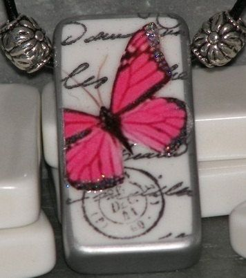 This domino pendant is decorated with stamped, french words and a pink butterfly image, just a touch of sparkles on the wings gives this piece a whimsical feel. It has a silvertone bead on each side, strung on a 19 black, leather cord with a lobster claw clasp and sealed with a clear sealer, If you need it in a different length, just let me know and I will be happy to change it for you.