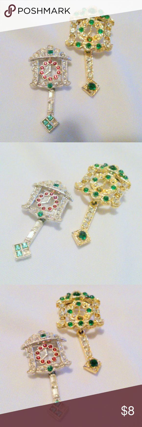 "Vintage Rhinestone Coo Coo Clock Brooches These two coo coo clock brooches are both articulated at the pendulum and are set with multi colored rhinestones. The larger one in done in a gold finish and is set with green and clear rhinestones. It measures 1 3/4"" in length by 7/8"" in width. The smaller one is done in a silver finish and is set with red, green and clear rhinestones and is missing one rhinestone at the end of the pendulum. It measures 1 7/16"" in length by 3/4"" in width. Circa…"