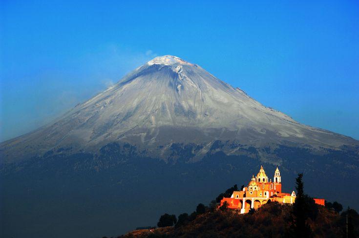 Den kæmpemæssige Popcatepetl vulkan ligger i udkanten af Pueblo i Mexico. Og her må man sige, at kirken Santuario de los Remedios har fået en fantastisk beliggenhed. Kirken ligger nemlig lige foran vulkanen og lyser op i landskabet med sin klare, orange farve.