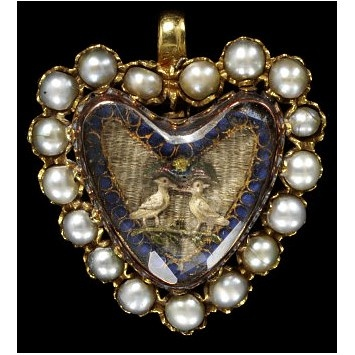 An English heart-shaped pendant, c.1700, set with pearls, with two embroidered love birds under a faceted crystal. (Victoria & Albert Museum)
