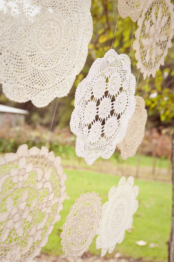 DIY shabby chic wedding backdrop with large lace doilies hung from tree branch.:
