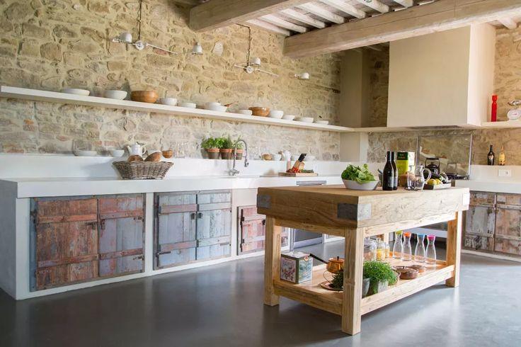Cucina muratura stile rustico - grande contrasto tra grezzo e superfici molto ben rifinite - muri in pietra, pavimento in cemento