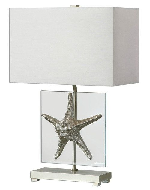 This modern art beach house 25 inch tall  lamp is created with a large metallic Silver Starfish Replica attached to a thick clear square glass plaque forming the base.