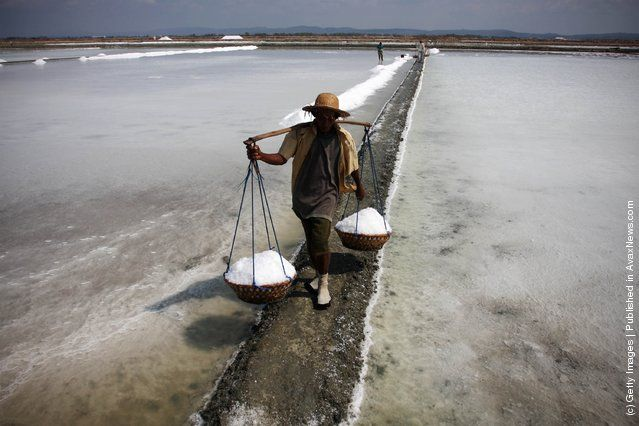 A farmer carries baskets of salt during a harvest in the the salt production process in Sumenep on Madura island, Indonesia
