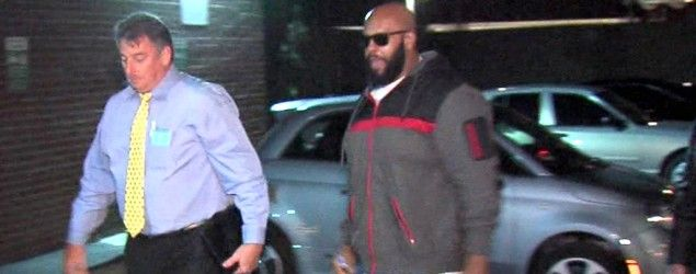 "This image from video shows Death Row Records founder Marion ""Suge"" Knight, right, walking into the Los Angeles County Sheriff's Department. (AP)"