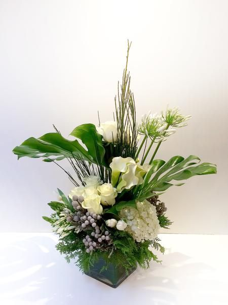 Tall and elegantarrangement on clear squareglassvase with all around look. A grand presentation of monstera leaves, white garden roses, star of bethlehem, gr