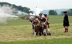 Several Continental soldiers firing muskets at the command of a General von Steuben reenactor.  Valley Forge, King of Prussia PA