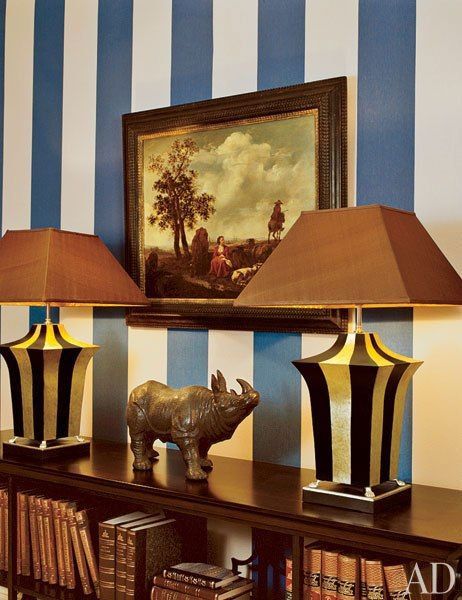 "Russian designer Dmitry Velikovsky mixed modern and traditional pieces in this Moscow pied-à-terre to create what his client described as ""a very simple space with a very complicated inside."" In the entrance hall, a 17th-century painting by Hendrik Mommers is offset by the blue-and-white striped wallcovering and equally bold lamps.  (August 2006)"